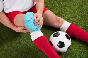 40394354 - close-up of a soccer player icing knee with ice pack on field